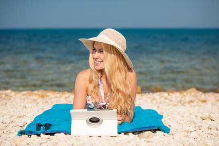 woman surfing internet looking at tablet on the beach. Stock Photo