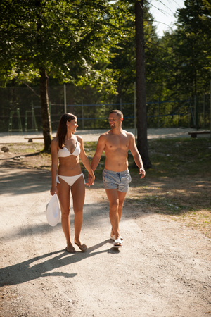 active young couple on a walk in park on summer morning Stock Photo