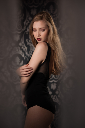 Boudoir photography of a beautiful young lady in black body over dark stylish background