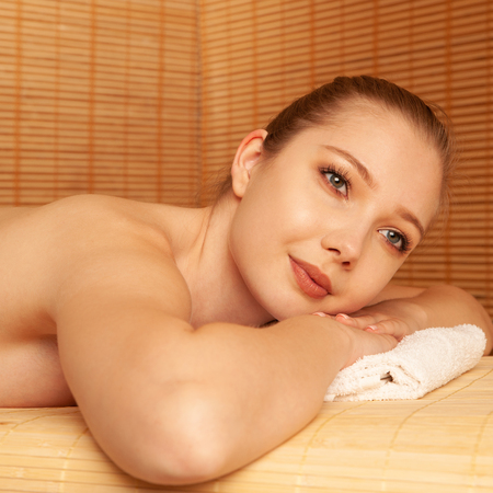 beautiful young Woman relax on massage table in spa salon . Stock Photo