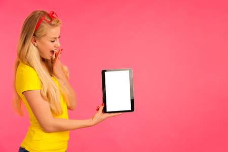 Beautiful young woman sin yellow t shirt holds tablet and surfs internet over pink background Stock Photo