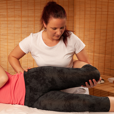 Physio therapy - therapist working on patient legs to increase mobility of joints after injury