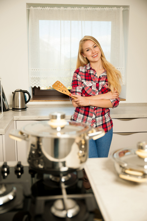 Beautiful young woman in kitchen cooks a delicious meal Stock Photo