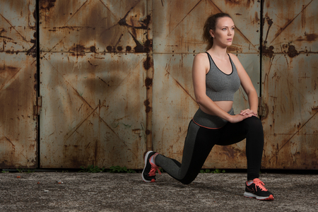 Beautiful young woman workout doing lunge step inear rusty door in industrial urban environment Stock Photo