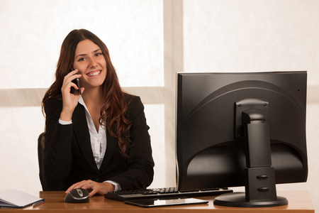 Beautiful business woman talks on the smart phone at desk in her office