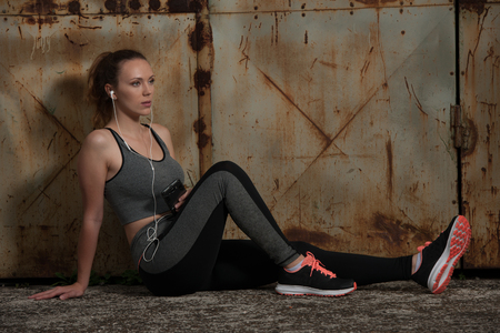 Beautiful young sporty woman listen music and relax near rusty industrial door in urban environment Stock Photo