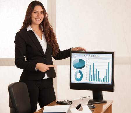 Beautiful business woman in her office with blank space on her monitor for additional text or graphic
