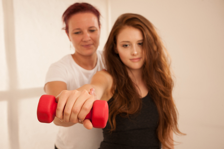 Physiotherapy - young woman making arm exercises with therapist for rehabilitation of injured arm Stock Photo