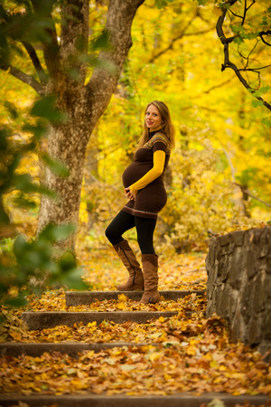 Beautiful pregnant woman outdoor in park on autumn afternoon with vibrant nature colors in background .