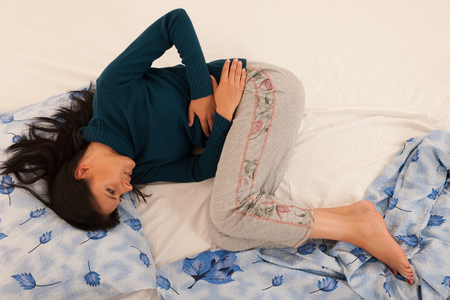 Young woman with stomach ache suffering isolated over white background . Stock Photo
