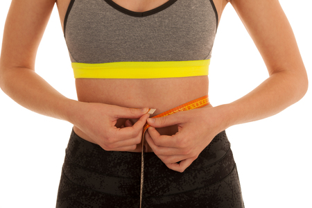 Beautiful fit woman measures waste isolated over white background Stock Photo