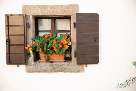 Small window of an old house with flowers Stock Photo