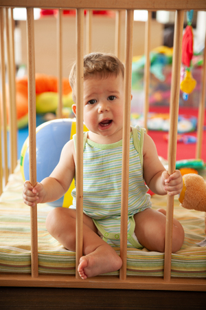 Cute smiling baby looking through the wooden bars of his crib or playpen with a happy smile indoors in the nursery Stock Photo
