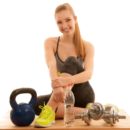 Beautiful young woman ready to workout with kettle and dumbbells . Stock Photo