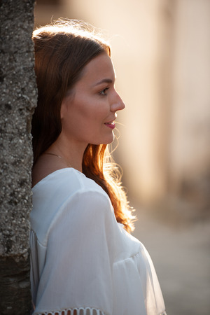 Outdoor portrait of a beautiful woman leaning on the wall