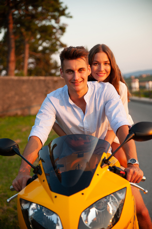 Young couple on a motor bike on a late summer afternoon Stock Photo