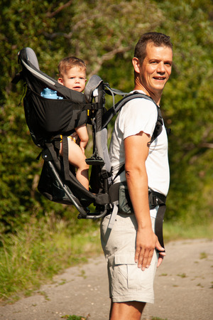 Father on a walk with kik in child carrier backpack . Stock Photo