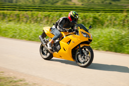Man drive a motorbike on a country road with vineyards in background . Stock Photo