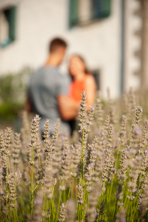 Young romantic couple standing on a garden near lavender plants