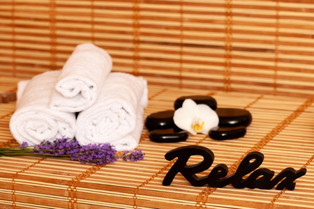 White towels and massage rocks in spa salon over dark and light bamboo background . Stock Photo