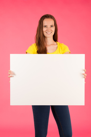 Young woman in yellow t shirt holds blank banner for advertisment over vibrant pink background