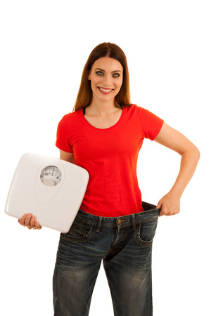 beautiful young woman holds too big trousers as she lost weight Foto de archivo
