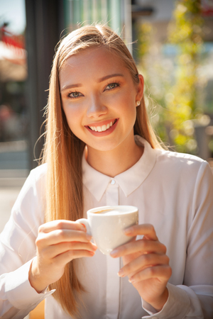 Business woman has a coffee break and drinks coffee in a bar