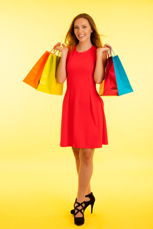 Beautiful young haapy woman in vibrant red dress holding shopping bags over yellow background