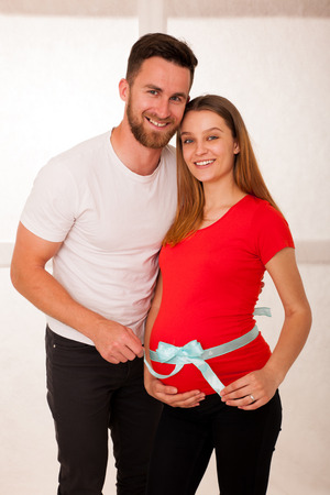 Pregnant woman and her man - studo photography of a young couple