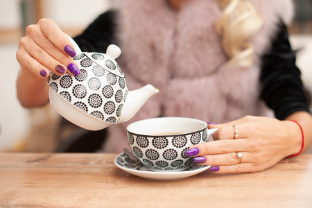 woman prepare  tea on bar terace hold teapot in her hands in early autumn .