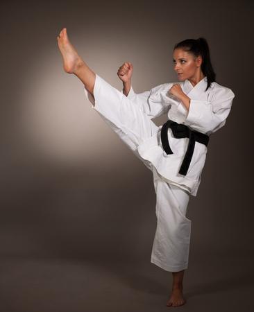 Woman in white  kimono kicks high in the air -  a karate  martial art girl