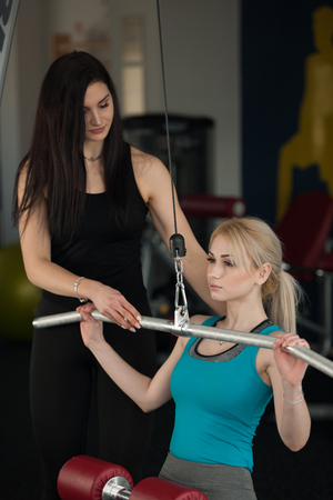 Beautiful blonde woman workout in fitness gim with her coach doing pull down exercises Stock Photo