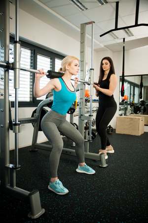 Beautiful young woman workout in fitness gym doing weighted squats with her coach
