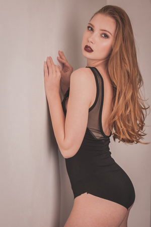 Boudoir photography of a beautiful woman standing near white wall in black body