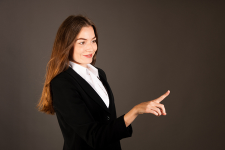 Attractive young business woman pressing virtual button over gray background