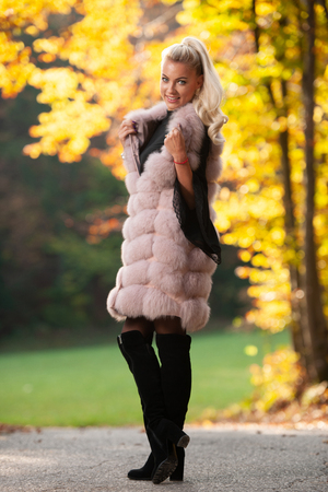 Beautiful stylish woman pose in park in early autumn  .