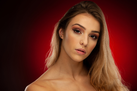Beauty portrait of a beautiful  young woman with brown long hair over dark red background .