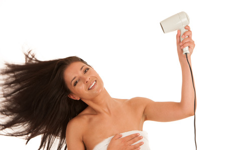 Beautiful young woman drying hair with hair dryer isolated over white background