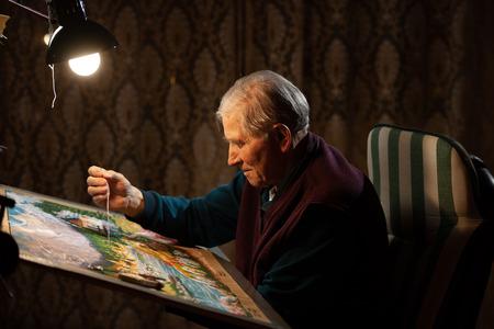 Elderly man woving a tapestry under bright light in living room on winter evening Stock Photo