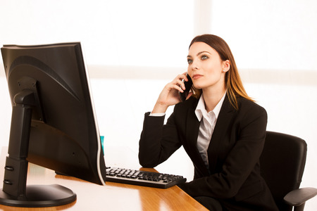 Beautiful business woman talks on smert phone in office at her desk