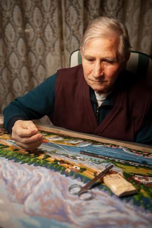 Elderly man woving a tapestry under bright light in living room on winter evening
