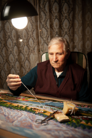 Elderly man woving a tapestry under bright light in living room on winter evening Stock Photo