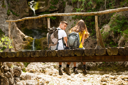 Active couple resting on a wooden bridge over mountain creek