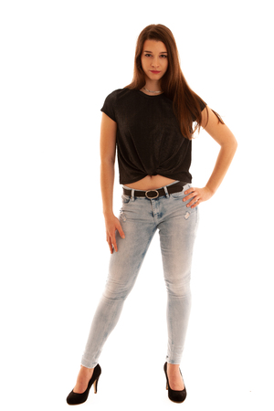 full length Portraiz of a beautiful caucasian teenage girl in black shirt and jeans isolated over white