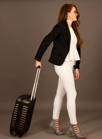 attractive busienss woman with suitcase - business travel studio conceptual photography