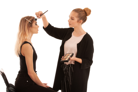 Young makeup artist doing makeup on a client over white background