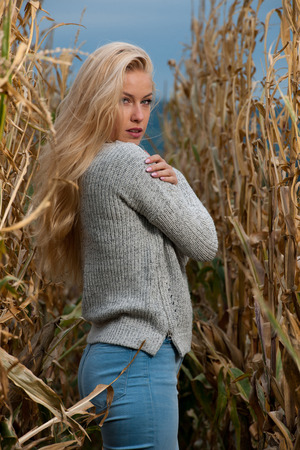 Blog style fashion photo of cute blond woman on corn field in late autumn