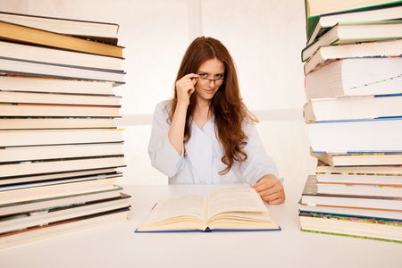 attractive young woman studies wtih hugr book piles on her desk Stock Photo