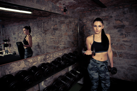 Beautiful young caucasian woman with black hair workout in fitness gym Stock Photo