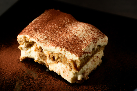 Piece of appetizing tiramisu cake on plate in close up Stock Photo